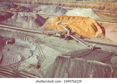 Brown coal deposits. Surface mine with exposed colored minerals and brown coal, mining equipment. View from above.