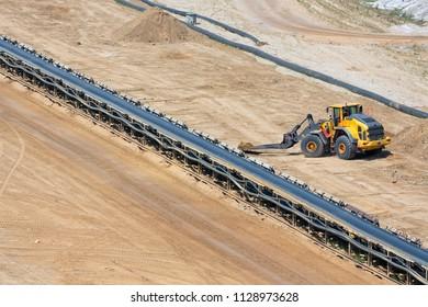 Brown coal open pit landscape with conveyor belt and dozer in Garzweiler mine Germany