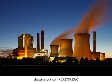 Braunes Kohlekraftwerk mit nachts blauem Himmel und Dampf.