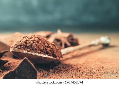 Brown cocoa powder in the spoon and chopped chocolate cubes, on dark background with copy space.