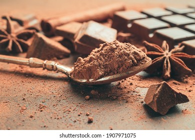 Brown cocoa powder in the spoon, chopped chocolate cubes and star anise on dark background.