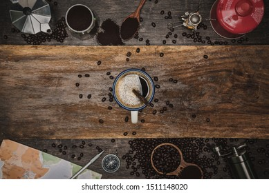 Brown coffee beans And a cup of hot coffee placed on a wooden table. Concept travel with map. Time to relax with a cup drink of good coffee. Top view copy space for your text.