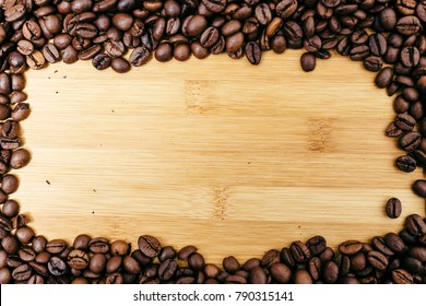 Brown coffee beans frame on a wooden board background