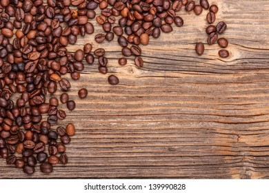 Brown coffee beans on vintage wooden background