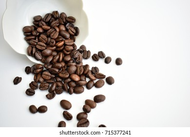 Brown coffee beans spilling out of decorative ceramic bowl onto table with bright white isolated background and negative editorial space to the right of image.