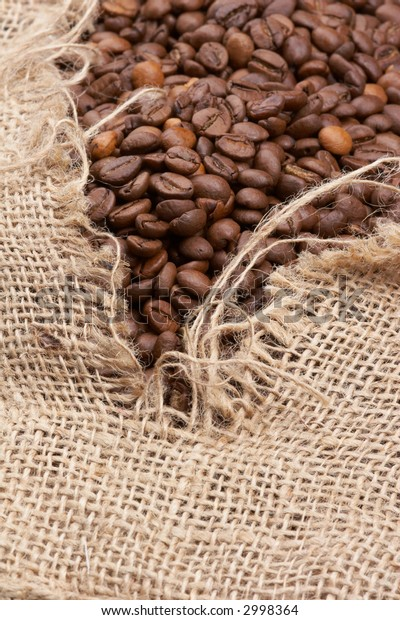 brown coffee beans in a tattered burlap sack