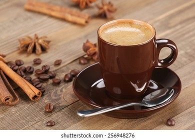 brown coffee cup in a saucer on the background of wooden planks
