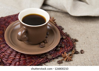 Brown coffee cups with saucers, coffee beans and cinnamon, bowk, star anise on sacking background, stand under hot, tray. Retro