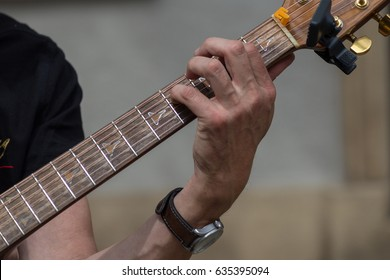 brown color of guitar body and fingers and hands of player are visible and strings as well