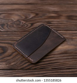 Brown colour handmade leather one pocket cardholder on wooden background. Stock photo with soft blurred background.