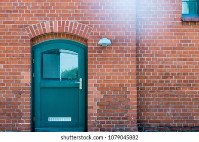 Brown concrete brick wall with black metal door in Berlin, Germany.