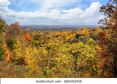 Brown County State Park in Indiana is renowned for it beautiful fall foliage vistas showing autumn leaves in many colors under a cloudy blue sky.