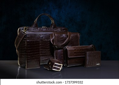 Brown crocodile leather men's accesories - handbag, purse; clutch, two wallets and belt on dark blue background. Fashion and shopping concept