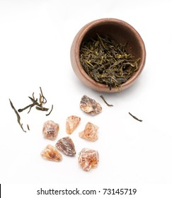 Brown crystal sugar and a tea cup with japanese green tea