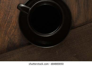 Brown cup of coffee and napkins on wooden table.