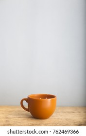 Brown cup of coffee on light wooden table and grey wall