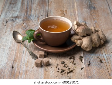 Brown cup of ginger tea with cubes of brown sugar, aged spoon, giner on side