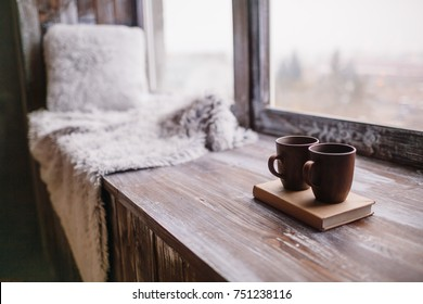 Brown cups stand on a book on wooden windowsill with blanket and pillow