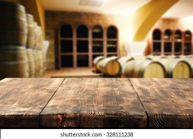 brown dark interior with barrels of wine and worn desk space