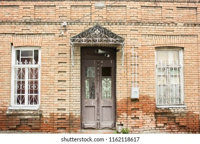 A brown door with a missing glass pane, on an orange brick wall.