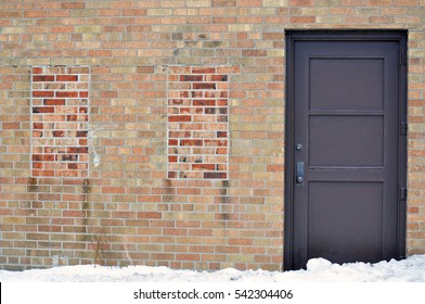 Brown Door Sitting Beside Two Bricked In Windows on an Old Building on a Winter's Day