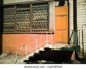 Brown door with stairs on brick old wall. Zaporozhye, Ukraine, 24 August 2018.