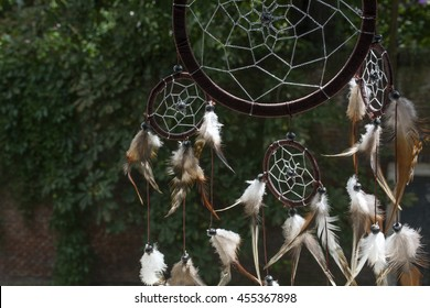 Brown dream catcher with green trees as background