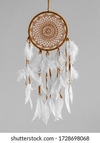A brown Dreamcatcher with white plumage on a gray background. Interior decoration. Native American Dream Catcher