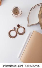 Brown earrings on the white desktop. Vertical