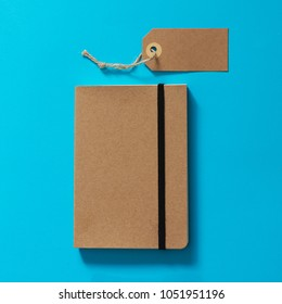 Brown eco label and notebook on a blue background. Mockup.