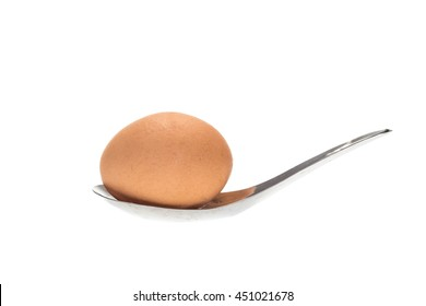 Brown egg in the spoon isolated on white