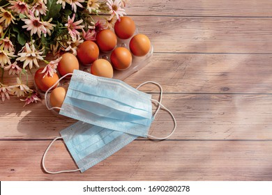 Brown eggs in box carton, medical mask and flowers on light wooden background. Concept of canceling the Easter holiday during the global pandemic. Flat lay, top view, copy space.