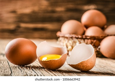 Brown eggs in carton box. Broken egg with yolk in background.