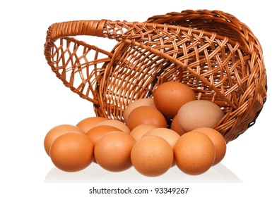 Brown eggs in the wicker basket over white background