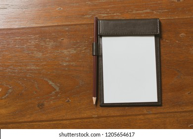 Brown empty white paper in restaurant payment billing receipt folder on granite table
