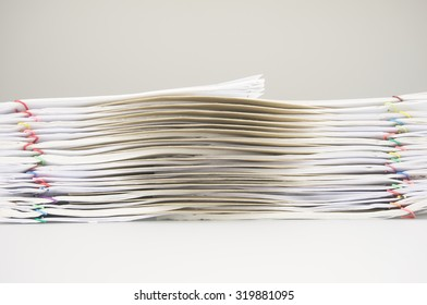 Brown envelope between overload of old paperwork place on table with copy space. Stack of paperwork is high as work hard. Business and finance concepts rich and successful photography.