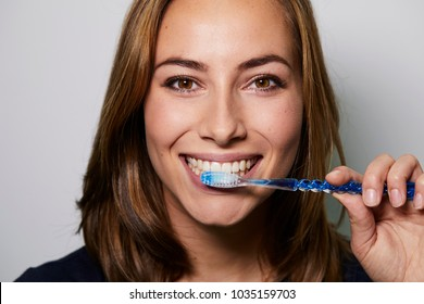 Brown eyed girl brushing teeth to camera, studio