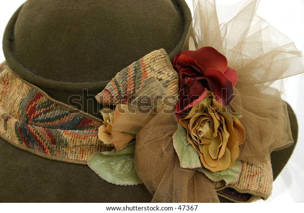 Brown felt hat with brown ribbon and floral decoration.