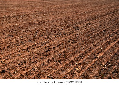 Brown, fertile, plowed soil of an agricultural field