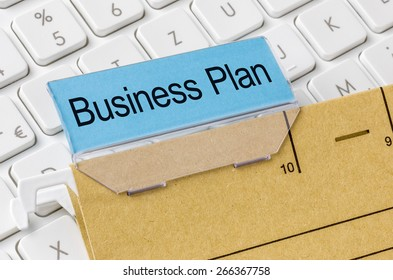 A brown file folder labeled with Business Plan