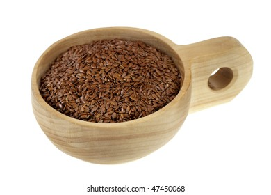 brown flax seeds on a rustic wooden scoop (cup), isolated on white