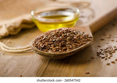 Brown flax seeds on a spoon and flaxseed oil  on a wooden table.