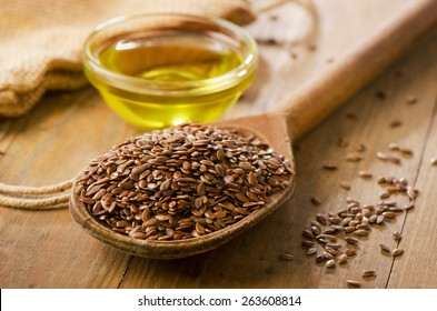 Brown flax seeds on a spoon and flaxseed oil.