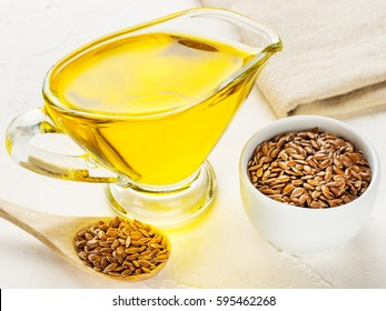 Brown flax seeds in spoon and flaxseed oil in glass jug on trendy textured white concrete background. Flax oil is rich in omega-3 fatty acid.