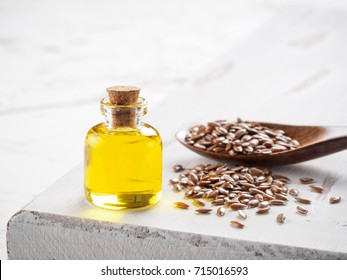 Brown flax seeds in spoon and flaxseed oil in glass bottle on white wooden background. Flax oil is rich in omega-3 fatty acid. Copy space.