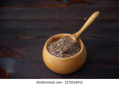 Brown flax seeds in wooden bowl and spoon on table.