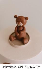 Brown fondant teddy bear on top of a cake.