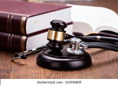 Brown Gavel With Medical Stethoscope Near Book At Wooden Desk In Courtroom