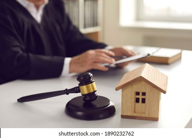 Brown gavel on sound block and small wooden house model on judge's table in courtroom during court hearing. Concept of real estate law, partition of property, separation of estates, divorce settlement