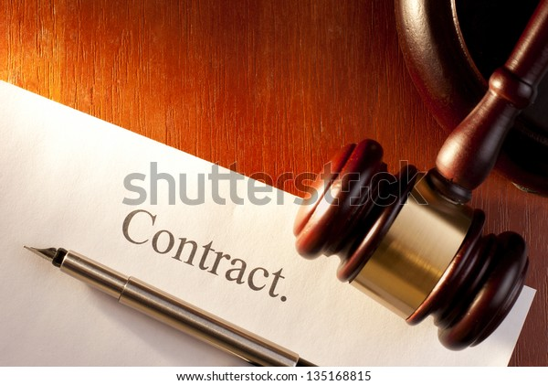 brown gavel on the table and the contract